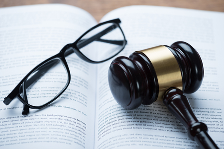 51090434 - high angle view of mallet and eyeglasses on open legal book in courtroom