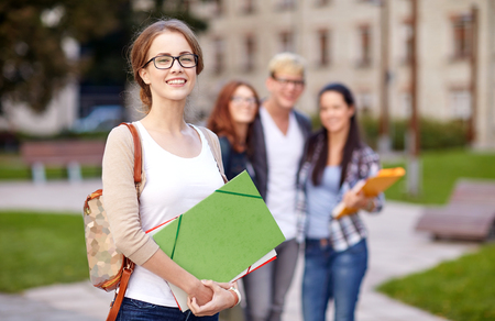 54720397 - education, campus, friendship and people concept - group of happy teenage students with school folders